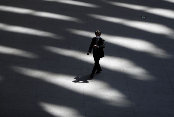 A man wearing a protective face mask, following an outbreak of the coronavirus disease, walks past inside an almost empty convention complex in Tokyo, Japan Quarentena global é evento inédito na história das pandemias 2020 04 06t054321z 487204696 rc2tyf9p06a0 rtrmadp 3 health coronavirus japan